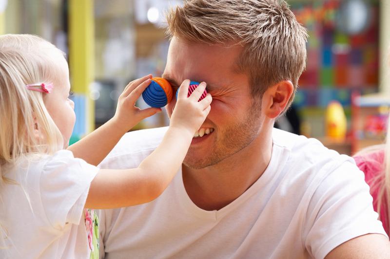 Tagesvater spielt mit Kind