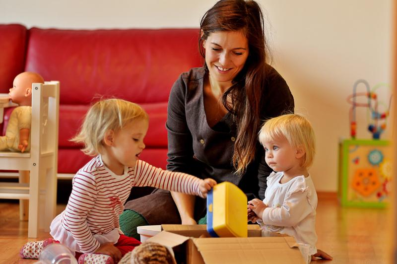 Betriebstagesmutter spielt mit zwei Mädchen