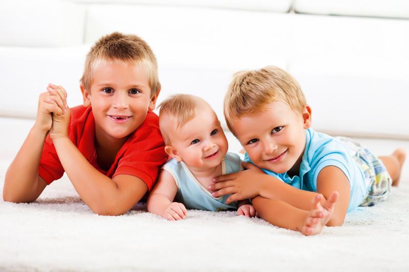 zwei Buben liegen mit einem Baby am Teppich