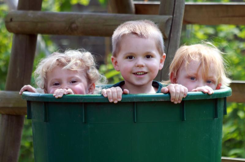 drei Kinder schauen aus der Regentonne heraus