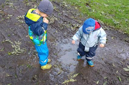 kinder spielen in wasserlacke